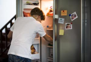 stres baiat deschide frigiderul_mancat pe baza de stres