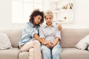 doua femei vorbesc pe canapea si se tin in brate