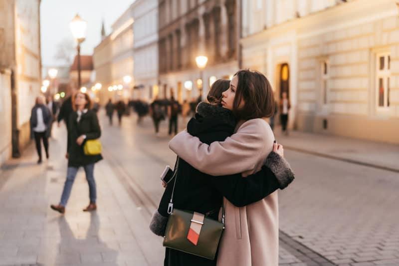 imbratisare empatica intre doua prietene