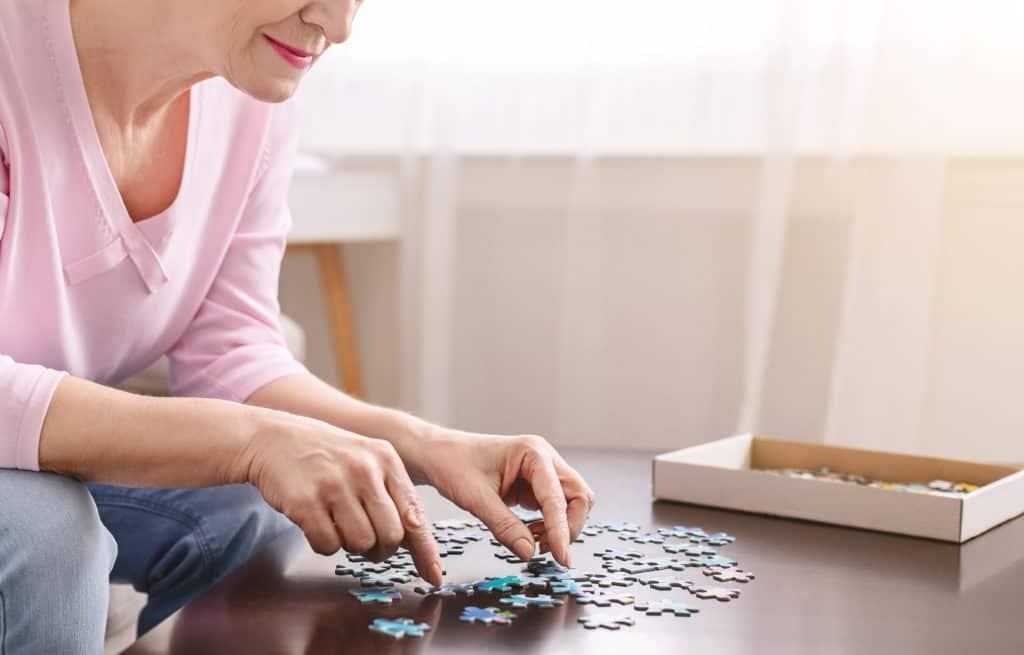 femeie care sufera de alzheimer si face puzzle