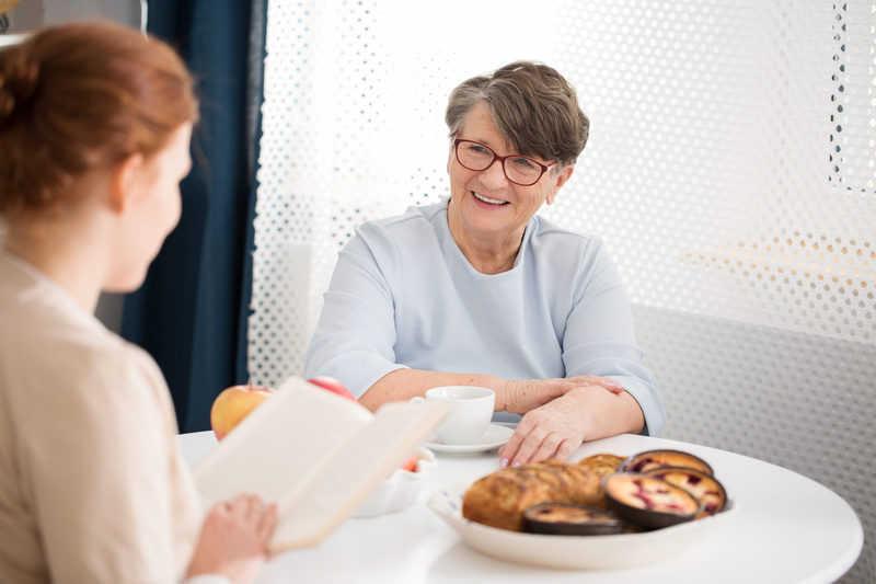 femeie in varsta care sta de vorba cu un asistent_dementa senila