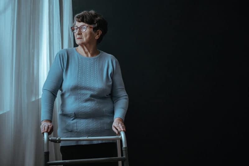 femeie in varsta care sta la geam_dementa